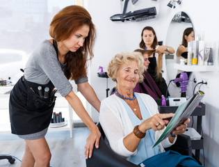Hairdresser with senior woman choosing hairstyling in magazine