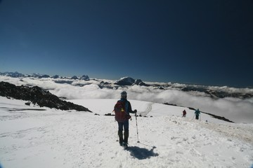 Tourist admires the Caucasus mountains from the slopes of mount Elbrus.