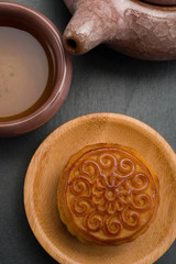 top view studio shoot of traditional Chinese mooncake with tea and teapot on black background vertical composition