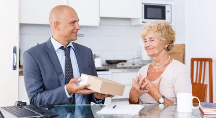 Sales representative passing box to woman