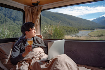 Young Asian man drinking beer and working with laptop computer on the bed in camper van with mountain scenic view through the window, digital nomad concept
