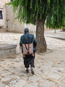 Tibetan man with braids, a striped back pack and traditional clothes walking near the Sera monastery, Lhasa, Tibet
