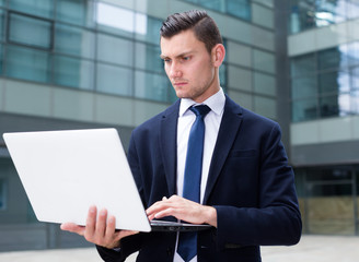Successful businessman is examining project on a laptop