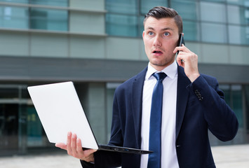 Young businessman is standing with laptop near the office