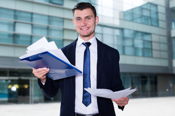 Serious employee is examining documents before signing