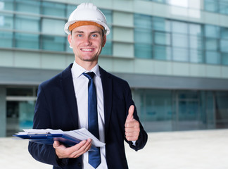 Smiling builder in suit and hat with folder is pleased with realisation his project