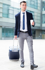 Male in suit with suitcase is drinking coffee