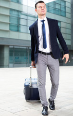 Adult man in suit with suitcase is staying