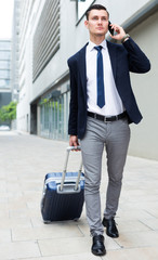 Successful man in suit with suitcase is talking by phone