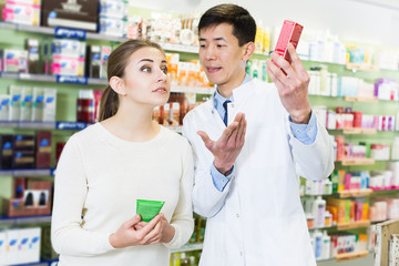 specialist  helping client choose medicine in pharmacy