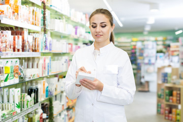 Woman pharmacist with notebook ,  stocktaking in  drugstore