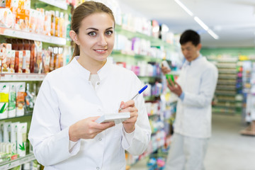 Female in uniform is  looking medicine with notebook  in pharmacy