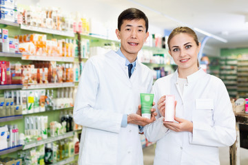 Two specialists are holding medicines and standing in hall of pharmacy.