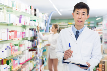 Chinese male is attentively looking medicine with notebook in apothecary