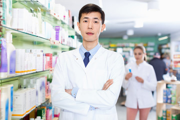 Portrait of chinese man pharmacist who is standing on his work place in apothecary.