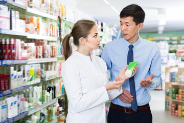 Adult man is asking pharmacist about medicines
