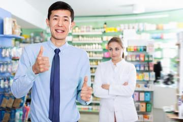 Portrait of smiling korean man client in pharmacy.