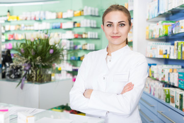 Positive woman pharmacist in uniform is standing in pharmacy