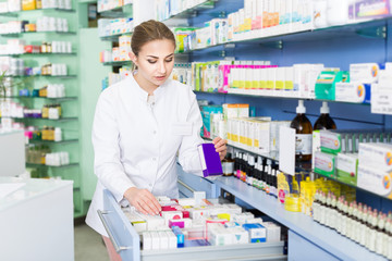 Woman pharmacist is attentively searching medicines in apothecary