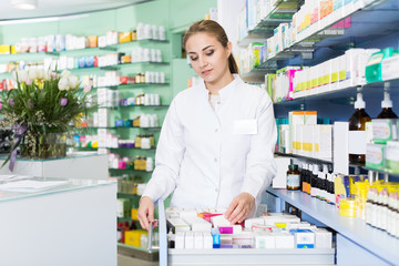 apothecary is searching medicine in drawers