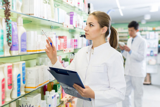 Woman pharmacist  looking medicine with notebook near shelves