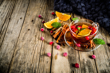 Autumn winter hot drink, cranberry spicy tea with orange, cinnamon and anise. On an old wooden background, with a warm blanket, copy space for text
