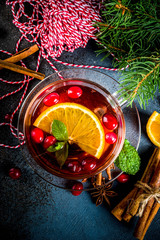 Papiers peints The Autumn winter hot drink, cranberry spicy tea with orange, cinnamon and anise. On an old wooden background, with christmas tree branches, copy space for text