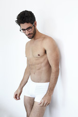 Muscular hunk in specs and shorts, looking down