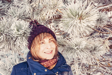 Young woman under the snowy coniferous tree