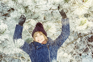 Young smiling woman under the snowy coniferous tree