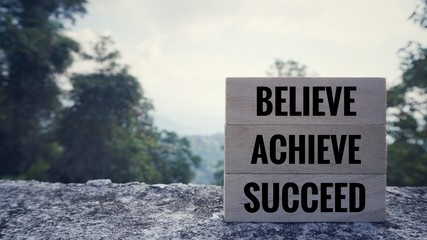 Motivational and inspirational quote - 'BELIEVE, ACHIEVE, SUCCEED' written on wooden blocks. Blurred styled background.