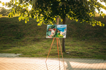 Picture on easel in the park. summer day