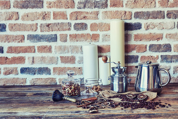 Still life with vintage coffee grinder and coffee beans on wooden table on brick wall background.