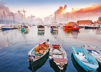 Spactacular sunset landscape of Santa Margherita Ligure-Portofino, Italy. Scene with fishing boats at foreground, epic dramatic cloudy sky in background. Ligurian sea beaches is luxury summer resort.