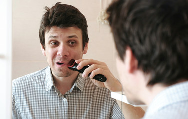 Machine shave facial hair. Young handsome man dry shaving with electric trimmer.