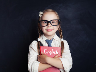 English concept with little schoolgirl student with pigtails and glasses. Smart kid learning english in language school