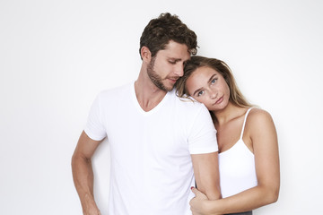 Loving couple in white clothing and studio, portrait