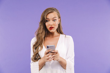 Photo of young brunette woman 20s with long curly hairstyle wearing dress holding and typing on smartphone, isolated over violet background