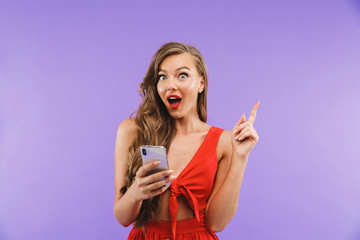 Image closeup of joyous excited woman 20s wearing red dress smiling and holding mobile phone, standing isolated over violet background