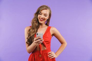 Image closeup of beautiful happy woman 20s wearing red dress smiling and holding mobile phone, standing isolated over violet background