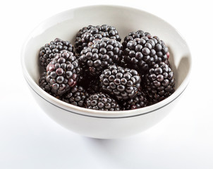 Delicious fresh blackberries and ripe black and reddish garnet. In white bowl and isolated background.