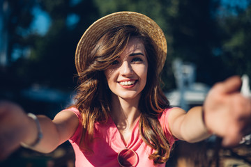 Close up portrait Nice laughing girl in hat making selfie on the beach.Cute summer fashion portrait of beauty brunette woman having fun