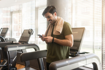 Young handsome man smiling while communicating through text messages on the mobile phone during break at the fitness club