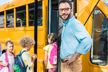 male teacher looking at camera while pupils entering school bus blurred on background