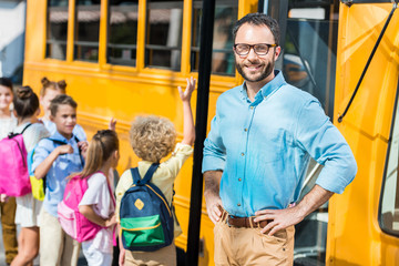 handsome bearded teacher looking at camera while pupils entering school bus blurred on background