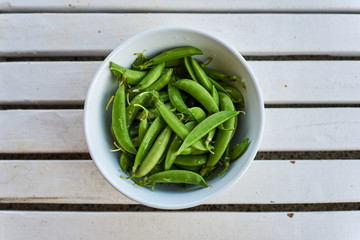 Fresh, young, unpeeled green peas in a glass plate.