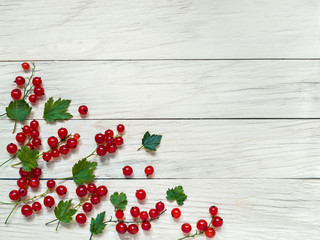 Red currant berries with green leaves lie on a plank background