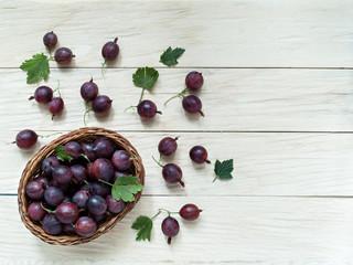 Fresh berries of gooseberries lie in a wicker basket on a wooden background