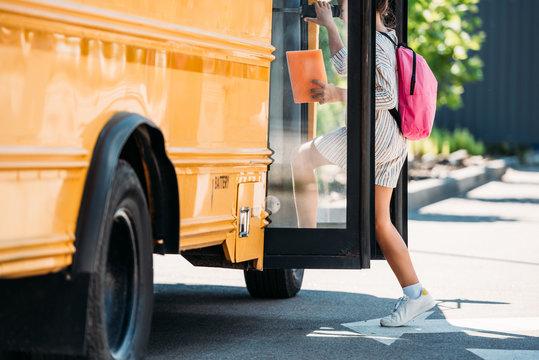 cropped shot of schoolgirl entering school bus