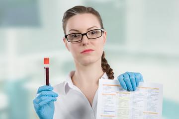Ärztin hält Blutprobe und Auswerteprotokoll in der Hand